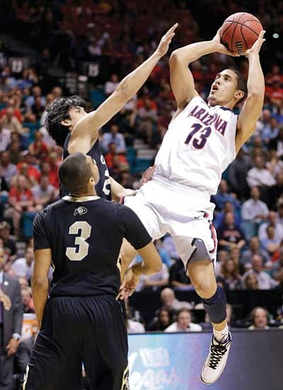 Julie Jacobson/The Associated Press<br> Arizona's Nick Johnson shoots against Colorado's Sabatino Chen and Xavier Talton in their Pac-12 tournament game Thursday in Las Vegas.