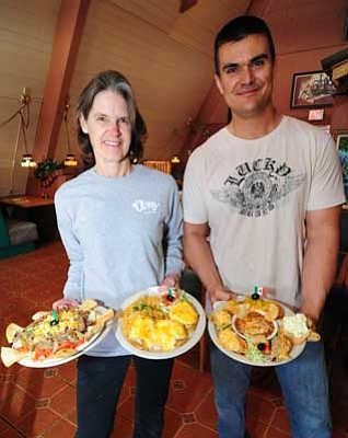 Les Stukenberg/The Daily Courier<br>  Eileen Olivas and her son, Tom, who is a part owner along with his wife, Cassi, hold three of their signature dishes.