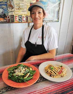 Matt Hinshaw/The Daily Courier<br>  Owner Judy May displays two of her favorite dishes, the Blackened Catfish with Chipotle Sauce and the Spinach Salad Wednesday afternoon in Prescott.