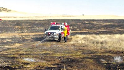 CVFD/Courtesy photo<br>A Chino Valley firefighter sprays a hot spot on a contained 50-acre wildfire Wednesday afternoon.