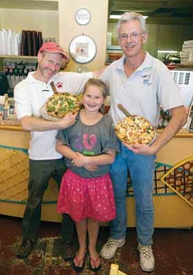 Les Stukenberg/The Daily Courier<br>  Jim Sobo, general manager, left, his daughter, Lucy, and owner Bill Tracy displaying the popular Elton John vegetarian pizza.