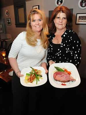 Les Stukenberg/The Daily Courier<br>   General Manager Wendy Price and manager Kelli Welch hold the fresh Atlantic Salmon and Prime Rib dinners at Murphy's Restaurant in Prescott Tuesday night.