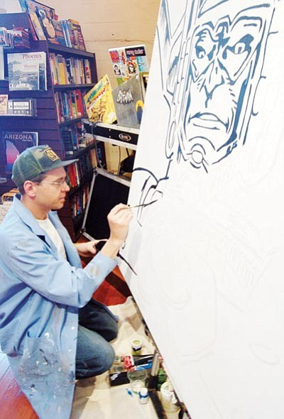 Patrick Whitehurst/The Daily Courier<br> Above, graphic designer Alan Huddleston paints Galactus at the Peregrine Book Company in Prescott while below, comic book artist Dave Beaty sketches superheroes at Game On in Prescott Valley Saturday as part  of Free Comic Book Day.