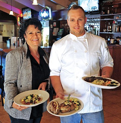 Prescott Steak House General Manager Terry Hawthorne and Head Chef Travis Keith display three of their favorite dishes, from left, Stuffed Portobello Mushroom, Rosemary Chicken with Smoky Loaded Potato, and the Ribeye with Garlic Mashed Potatoes. (Photo by Matt Hinshaw/The Daily Courier)