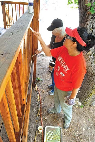 Matt Hinshaw/The Daily Courier<br> Judy Olea, near, and Shari Noe stain the wood railing on a porch at the home of Jimmy and Tamara Grawey Thursday morning during Keller Williams Check Realty Red Day in Prescott. Real estate agents from Keller Williams and other volunteers cleaned and fixed up the Grawey home.