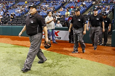 Mike Carlson/The Associated Press<br>Umpire Fieldin Culbreth, left, leads his crew onto the field prior to a game between the Padres and Rays on May 10 in St. Petersburg.