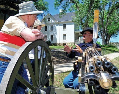 "Matt Hinshaw/The Daily Courier<br> Gary Harper, a historian and gun collector, talks with Richard and Bi Sallomi about his original 1874 Gatling gun – which he used when he appeared in the 2003 Tom Cruise movie ""The Last Samurai"" – during the Fort Whipple Museum's ""Ordnance: Bullets, Bayonets and Firearms"" event Saturday afternoon."