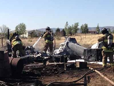 Courtesy Chino Valley Fire District<br> A wildland fire burned several outbuildings in Paulden on Sunday afternoon after the wind lifted sparks from a burn barrel, igniting grass and weeds.