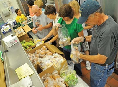Matt Hinshaw/The Daily Courier<br> From left, Everett Sanborn, Kathy Eiskamp, Lorraine Tirrell, and John Gage, volunteers with Prescott Area Leadership, put together sack lunches for students as part of the 2011 Hungry Kids Project.