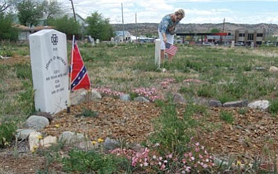 Joanna Dodder/The Daily Courier<br> Yavapai Cemetery Association volunteer Norma Read places flags on veterans' graves at the historic Citizens' Cemetery in Prescott, in preparation for the Memorial Day observance.