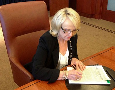 Jeff Dial/The Associated Press<br>Gov. Jan Brewer signs a proclamation calling the Legislature into special session Tuesday in Phoenix.