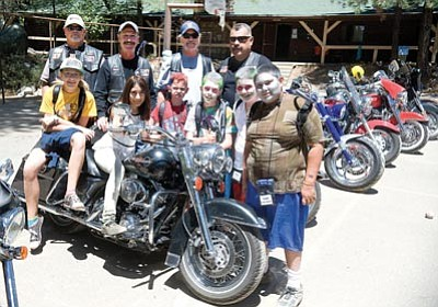 """Les Stukenberg/The Daily Courier<br>Members of the Wind and Fire Motorcycle Club Whiskey Row Chapter, from left, Verde John, Les Roberts, Santa Fe Dave and Charlie Reyes pose with some of the campers at """"Camp Courage,"""" the annual Arizona children's burn camp, taking place this week at Pine Summit Camp south of Groom Creek."""