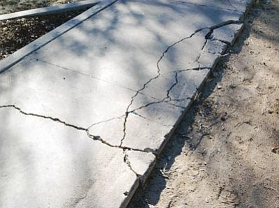 Courtesy photos<br>Above, cracked concrete plagues Granite Mountain Middle School, while below, damaged roofing is seen at Prescott High School. More than $8,000 of a proposed $28 million bond would go toward roofing, concrete and asphalt repair, according to school officials. Voters will be asked to approve the bond, as well as an override totaling more than $2 million, in November.