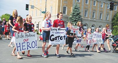 Les Stukenberg/The Daily Courier<br>Relatives of the fallen firefighters honor the men from the Granite Mountain Hotshots during the 72nd annual Kiwanis Kiddie Parade on Cortez Street in Prescott Friday morning.