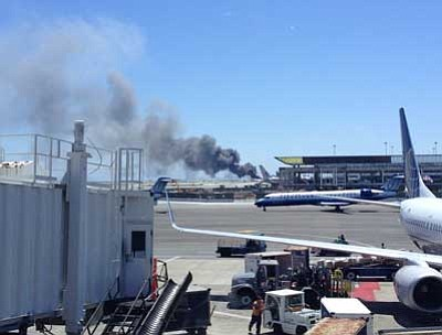 Zach Custer/The Associated Press<br> Smoke rises from what a federal aviation official says was an Asiana Airlines flight crashing while landing at San Francisco airport on Saturday. It was not immediately known whether there were any injuries.