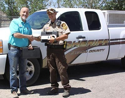 Courtesy photo<br>Yavapai Humane Society executive director Ed Boks presents Yavapai County Animal Control Officer Jake Lane with two microchip scanners to help quickly return lost pets to their owners. Contact YHS about how you can get your pet microchipped – which may save his/her life.