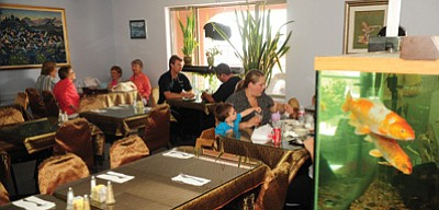 Les Stukenberg/The Daily Courier<br>   Lunch diners enjoy their food at Tara Thai II in Prescott Valley.  Below, owners Rex and Ting Cullum hold a dish of pad Thai, one of the restaurants most popular offerings,