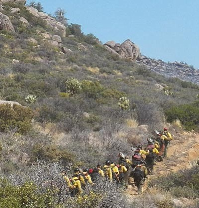 Joy Collura/Courtesy photo<br> The Granite Mountain Hotshots climb a mountain on the morning of June 30 to fight the Yarnell Hill wildfire.