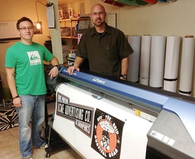 Ken Hedler/The Daily Courier<br>Jeremiah Sawyer, left, manager of Acme Advertising LLC in Prescott, and Lee Divelbiss, part-owner of the company, display logos that they printed on a Roland VersaCamm. Divelbiss and two partners opened Acme and The Tech Center April 1 at 711 Miller Valley Road, and share the building with another company of which he is a part-owner: Off the Grid Survival Gear.