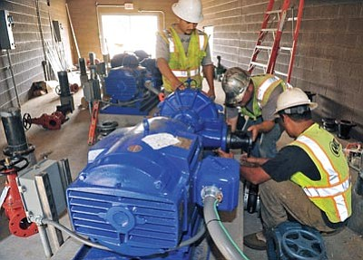 Matt Hinshaw/The Daily Courier<br>Pipefitters with CLM Earth Movers check pipe fittings on one of the water pumps inside the new City of Prescott Zone 27 pumphouse near Gurley Street Wednesday afternoon.