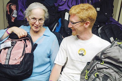 Patrick Whitehurst/The Daily Courier<br> Diane Iverson and CCJ director for development Michael Dummeyer sit before a mountain of backpacks collected for the organization's Fair Start program.