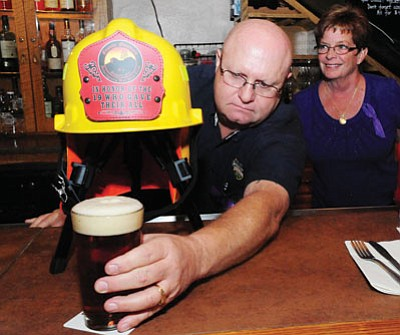 Les Stukenberg/The Daily Courier<br> Prescott Brewing Company owners John and Roxane Nielsen pour the first glass of the Heroes 19 beer Monday. All proceeds from the sale of the beer, no matter where it is sold, will be donated to the Prescott Firefighters Charities.