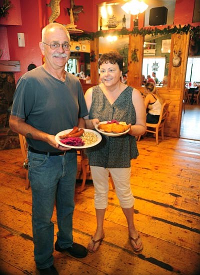 Les Stukenberg/The Daily Courier<br> Owners Mikolaj Bijan and Zita Brink display one plate containing bratwurst, spatzle and red cabbage, and another plate with schnitzel and croquettes. They bring European cuisine to the Prescott area.
