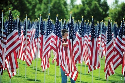Les Stukenberg/The Daily Courier<br> Paul Gersper, a Korean War veteran and member of American Legion Post 106, straightens some of the 3,000 American flags at the Prescott Valley Civic Center Healing Fields. The flags honor those lost on 9/11, in wars and other tragedies.