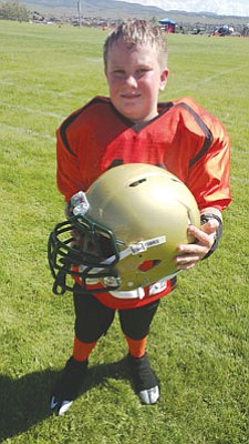 Ed Wisneski/Courtesy<br>Justus Black, a fourth grader at Abia Judd who competes in the Prescott Valley Youth Football and Cheer Association, poses with his Revolution ® IQ HITS ™ Helmet, manufactured by Riddell. A look inside reveals six sensors built into the lining that measure the movement of Justus's head, not the helmet.