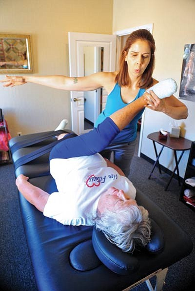 Matt Hinshaw/The Daily Courier<br> Holly Thompson, owner of His n Hers Pilates, performs Fascia Stretch Therapy on May Smith's lower body Thursday morning.