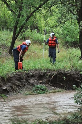 Wade Ward, Prescott Fire Department/Courtesy photo<br> Rescue workers search for a body in Granite Creek Aug. 26 after monsoon-related flooding.