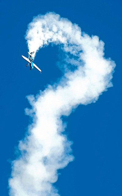 Matt Hinshaw/The Daily Courier<BR> Embry-Riddle Alumnus Melissa Pemberton performs a hammerhead, above, during her aerobatic routine Saturday morning at the ERAU Wings Out West Air Show at the Prescott Airport. Below, Pemberton cuts a ribbon with the tail of her inverted aircraft.