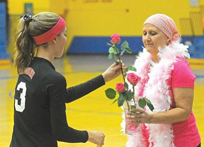Matt Hinshaw/The Daily Courier<br>Bradshaw Mountain High School's Emma Williams (3) puts a pink rose in a vase showing her support for Prescott High School volleyball coach Shellie Bowman before the Prescott-Bradshaw game Tuesday night at PHS.  Players, fans, and coaches were dressed in pink to support Bowman's battle with breast cancer and also for the Breast Cancer Awareness volleyball match.