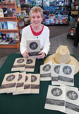 "Patrick Whitehurst/The Daily Courier<br /><br /><!-- 1upcrlf2 -->Author Pat Parish holds a copy of ""Dutchman and the Devil: The Lost Story"" during a signing at Hastings in Prescott Saturday. <br /><br /><!-- 1upcrlf2 -->"