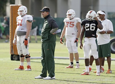 Wilfredo Lee/The Associated Press<br> Miami head coach Al Golden, second from left, watches a drill during team practice on Tuesday in Coral Gables, Fla. Miami's football team will lose nine scholarships and the men's basketball team will lose three, as part of the penalties the school was handed Tuesday by the NCAA as the Nevin Shapiro scandal presumably drew to a close.
