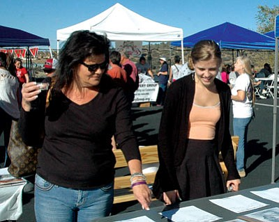 Tamara Sone/The Daily Courier<br> Attendees at Sunday's Hotshot Girls' benefit peruse some of the more than 70 silent auction items. The wives, fiancées and other family members of the 19 fallen Granite Mountain Hotshots hosted the event at the new Celtic Crossings.