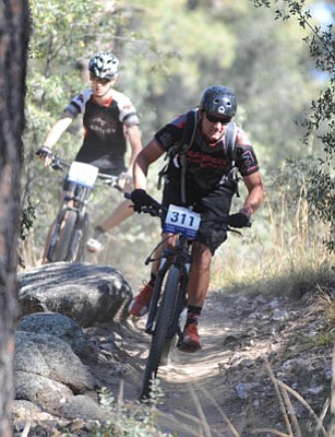 Les Stukenberg/The Daily Courier<br>Bradshaw Mountain's Macklin Walter takes an agressive line down the trail during the Arizona High School Mountain Bike League race at the White Spar Campground in Prescott Sunday.