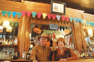 Cindy Barks/The Daily Courier<br>Jersey Lilly Saloon's annual fundraiser for the Courthouse Lighting will officially kick off Thursday evening, but donations have already been coming in. Here, saloon owners Tommy and Joan Meredith stand in front of the bar, which displays some of the bulbs listing the donors, as well as the Steve Atkinson painting that will be raffled off as a part of the fundraiser.