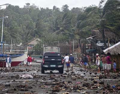 Nelson Salting/The Associated Press<br> Debris litters the road by the coastal village in Legazpi city after a storm surge brought about by powerful Typhoon Haiyan in Albay province Friday, about 325 miles south of Manila, Philippines.