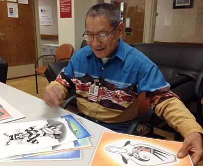 The Daily Courier<br> Davis Honie, a Marine veteran (inset, above), shows off some of the Native American-inspired drawings that he creates. Honie draws each piece freehand without the aid of rulers.