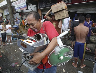 AP photo<br> A Filipino resident reacts after getting supplies from a grocery that was stormed by people in Tacloban city, Leyte province, central Philippines on Sunday. The city remains littered with debris from damaged homes as many complain of shortages of food and water and no electricity since Typhoon Haiyan slammed into their province.