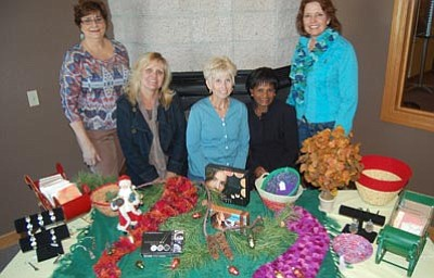 Joanna Dodder/The Daily Courier<br> Community Pregnancy Center Director Mary Kay Asche, left, shows off holiday boutique items alongside boutique organizers (left to right) Bev Kosharek, Pam Streetman, Maria Meager and Susan Stanfill.