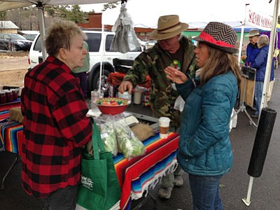 Tamara Sone/The Daily Courier<br> Whipstone Farm owners Cory and Shanti Rade, on right, talk to a customer about their produce. Each weekend, the Rade's bring out a variety of fruits and vegetables from their farm in Paulden to showcase at the Winter Farmers Market.