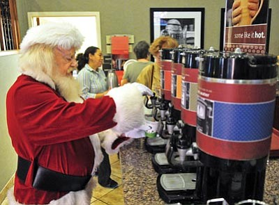 Matt Hinshaw/The Daily Courier<br>Santa Claus grabs a cup of coffee from the Hampton Inn lobby before heading to the Prescott Gateway Mall Saturday.