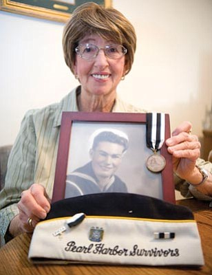 Les Stukenberg/The Daily Courier<br>Connie Lyon holds a photo of her husband Bill Lyon, a Pearl Harbor survivor who served in the Navy as a torpedoman 3rd class on the USS Detroit.