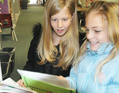 Patrick Whitehurst/The Daily Courier<br> Abia Judd Elementary School 4th graders Brekyn Waples and Morgan Engels (right) sort holiday mail to be delivered to other students at the school. The holiday post office is an annual tradition at the Prescott School.