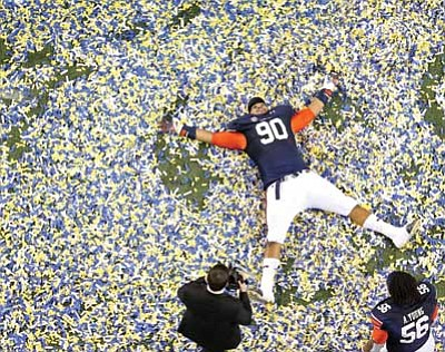Jason Getz, Atlanta Journal-Constitution/The AP<br> Auburn defensive tackle Gabe Wright does snow angles in confetti after Auburn's 59-42 win over Missouri in the SEC Championship Saturday night in Atlanta.