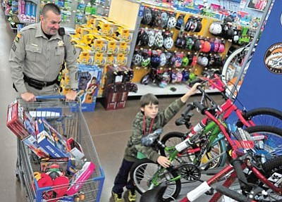 Matt Hinshaw/The Daily Courier<br>Jonathan Willey, 10, checks out a bike while Department of Public Safety Sergeant Steve Mitchell looks on Saturday morning during the 16th annual Shop with a Cop event at the Gail Gardner Walmart in Prescott.