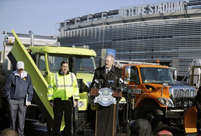 Mel Evans/The Associated Press<br>Alfred F. Kelly, Jr., left, President and CEO of the NY/NJ Super Bowl Host committee, and NJ department of transportation deputy commissioner Joseph Mrozek, center, stand near large snow plows as they listen to President and CEO of MetLife stadium, Brad Mayne, answer a question at MetLife stadium in East Rutherford, N.J., on Wednesday. Officials were demonstrating snow removal and melting machinery, and outlining emergency weather scenarios and contingency plans for the Super Bowl in February.