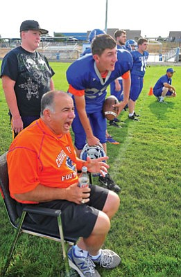Matt Hinshaw/The Daily Courier<br>Chuck Apap yells and cheers, letting his players know they ran their play well while quarterback Bud Cain looks on Aug. 9 during team practice in Chino Valley this past preseason. After 43 years of coaching, Apap officially retired Thursday.